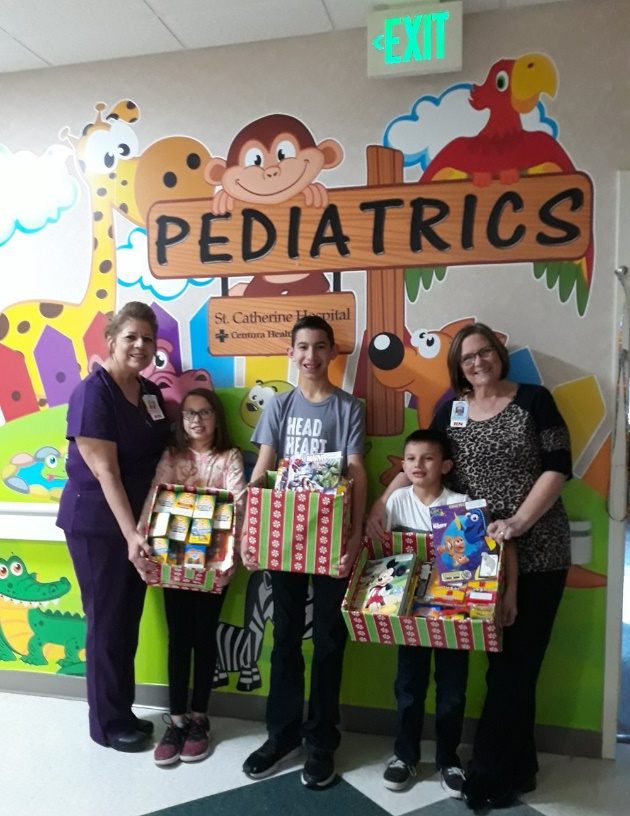 The Morales family dropped off their donation of nearly 85 coloring books and sets of crayons for the St. Catherine Hospital Maternal Child Department on December 3. Pictured, from left to right, are Maternal Child Assistant Nurse Manager Valerie Schuetz, Abigail Morales, Aaron Morales, Andrew Morales and Maternal Child Director Jill Robinson.